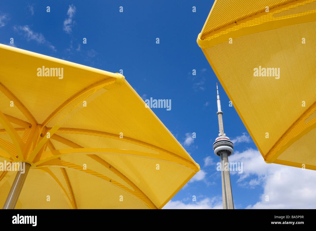 Toronto CN tower between two yellow metal beach umbrellas at urban beach of HTO Park - Stock Image