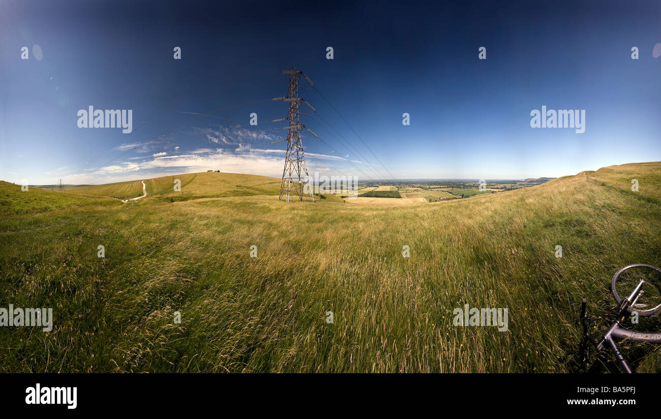 Electrical power lines suspended from pylons cross the South Downs Way at Fulking, West Sussex, UK - Stock Image