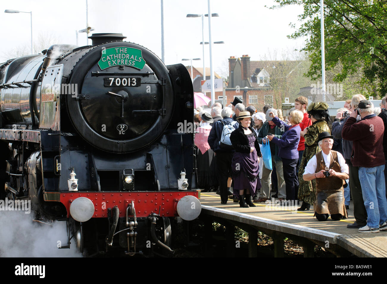 Oliver Cromwell steam engine pulling The Cathedrals Express train into Petersfield railway station crowded platform - Stock Image