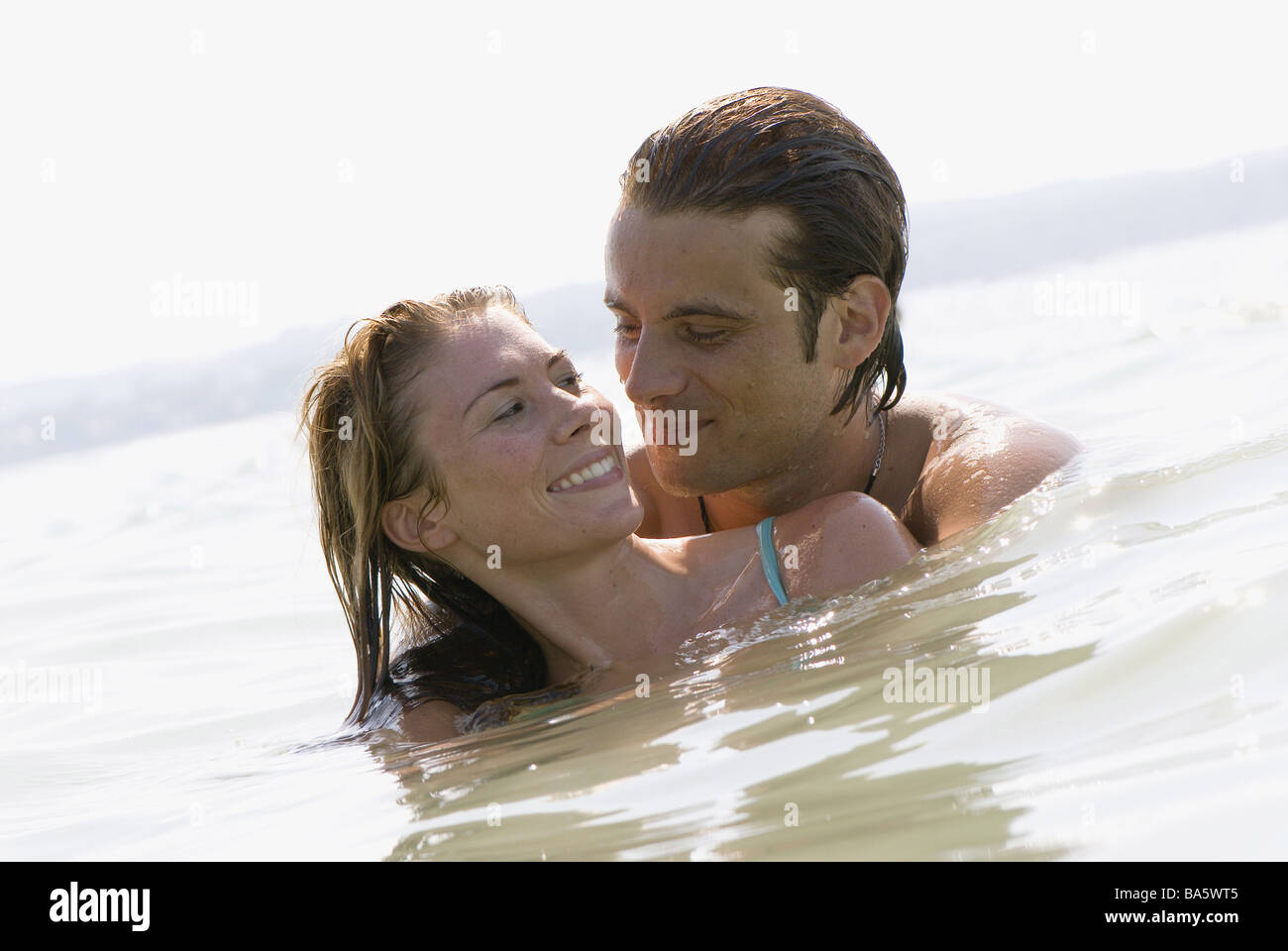 Sea pair water falls in love stands love-pairs embrace smile gaze-contact portrait series people love proximity - Stock Image