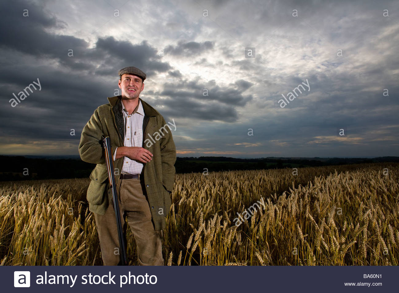 Portrait of hunter with rifle standing in wheat field - Stock Image