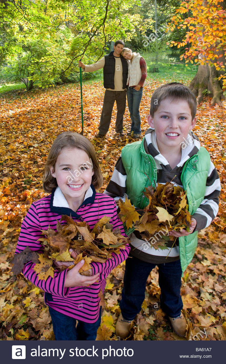 Portrait of boy and girl holding autumn leaves with parents in background - Stock Image