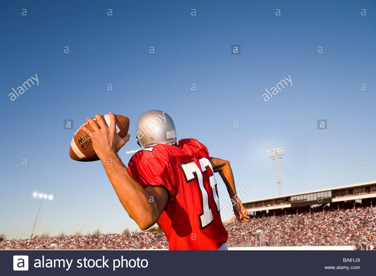 Quarterback throwing football - Stock Image