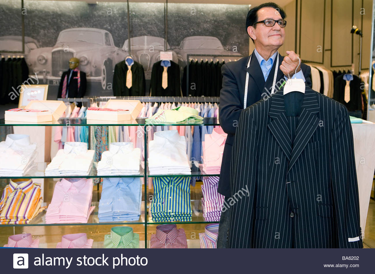 Male tailor in shop holding suit jacket, smiling - Stock Image
