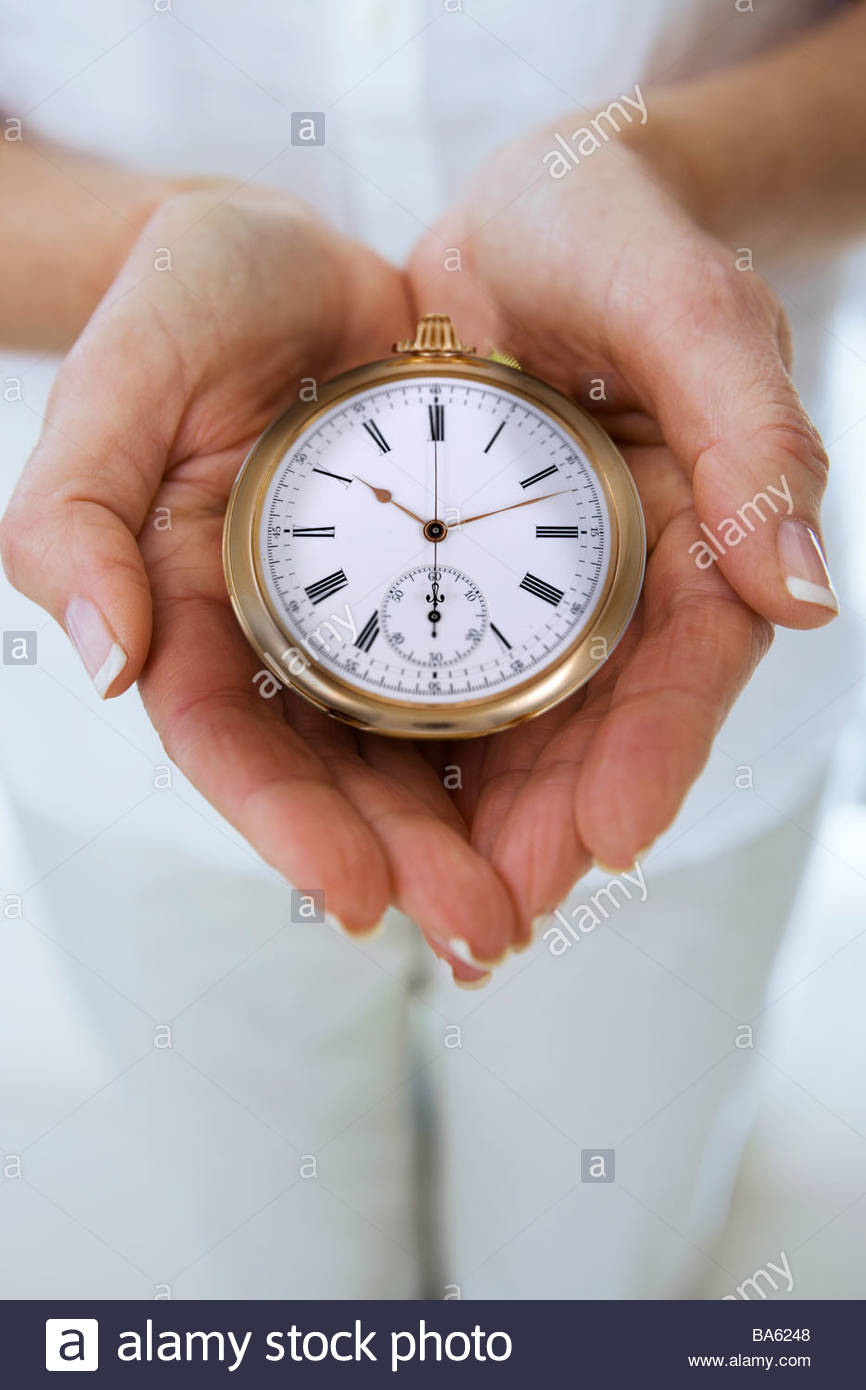 Close up of womanís hands cupping stopwatch - Stock Image