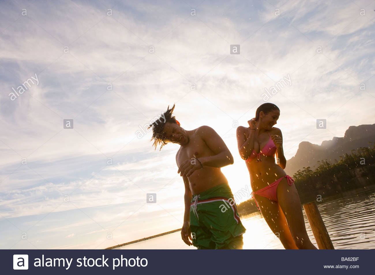 Couple in bathing suits shaking water off bodies - Stock Image