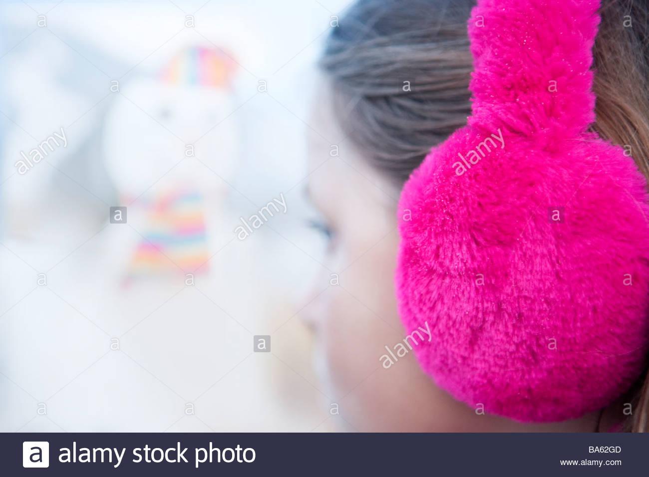 Close up of girl wearing bright pink earmuffs - Stock Image
