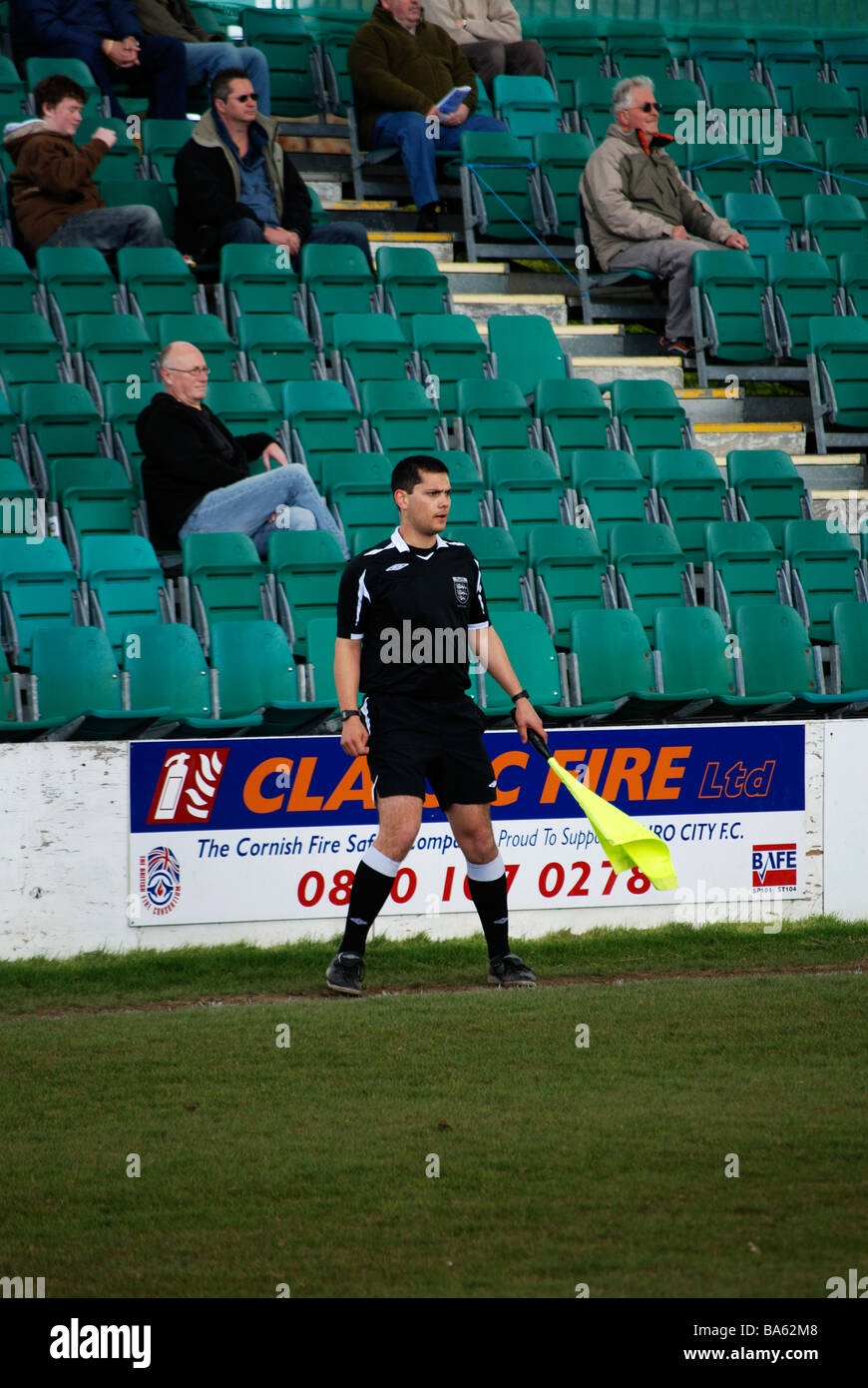 a referees assistant running the line at a football match - Stock Image