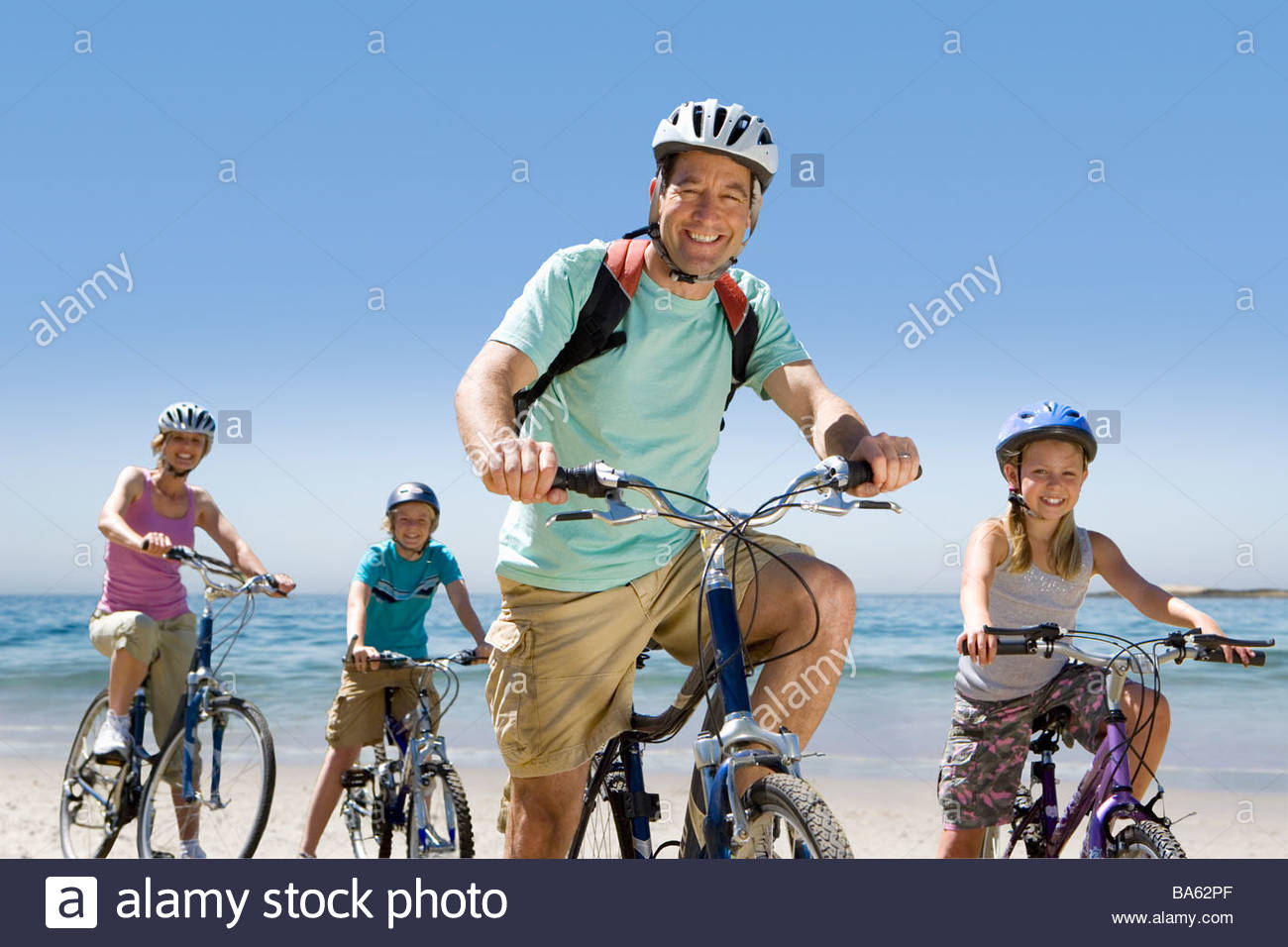 Portrait of family riding bicycles on beach Stock Photo