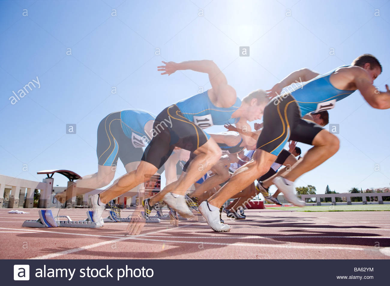 Runners emerging from starting block in multiple exposure - Stock Image