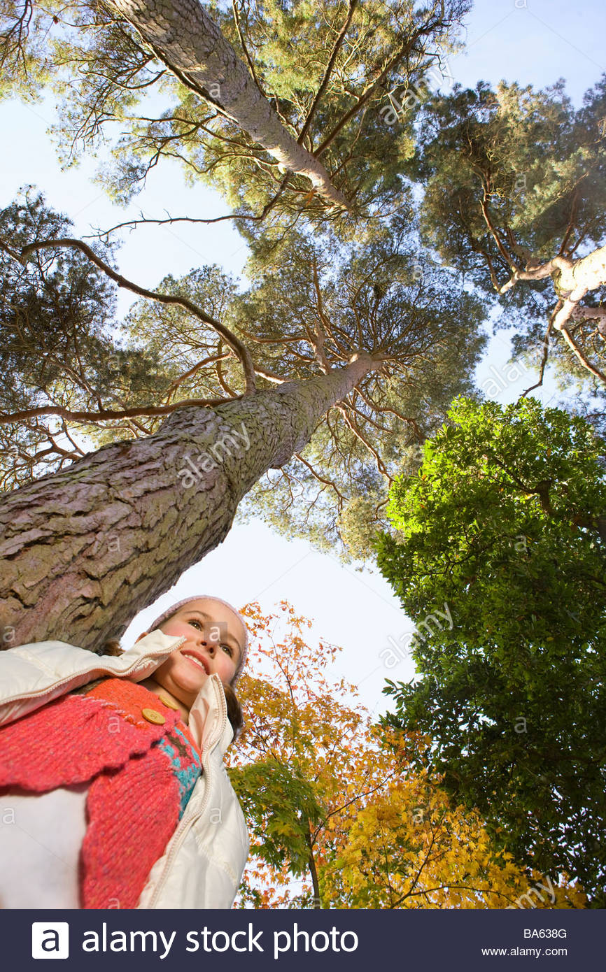 Girl standing under tall tree - Stock Image