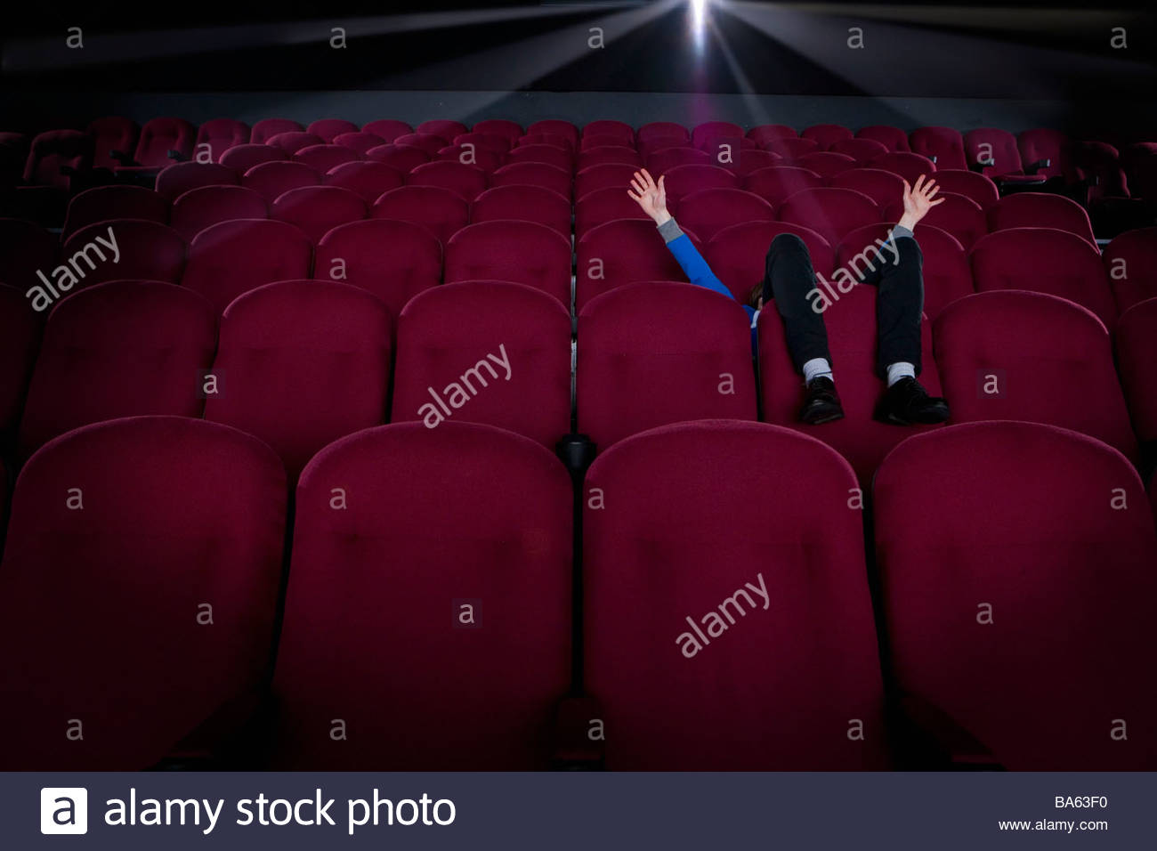 Man in empty cinema, face obscured, arms raised - Stock Image