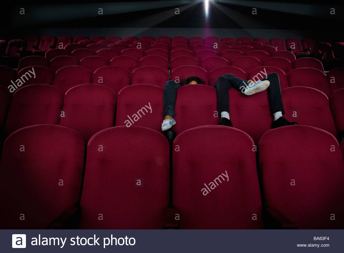 Couple in empty cinema, legs over seats, faces obscured - Stock Image