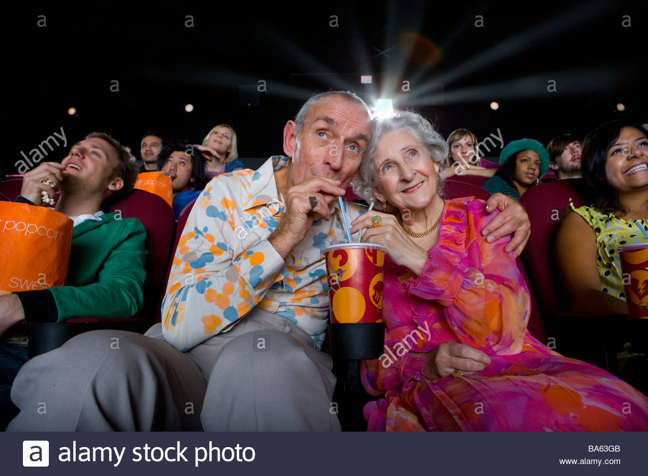 Senior couple sharing drink in cinema, low angle view - Stock Image