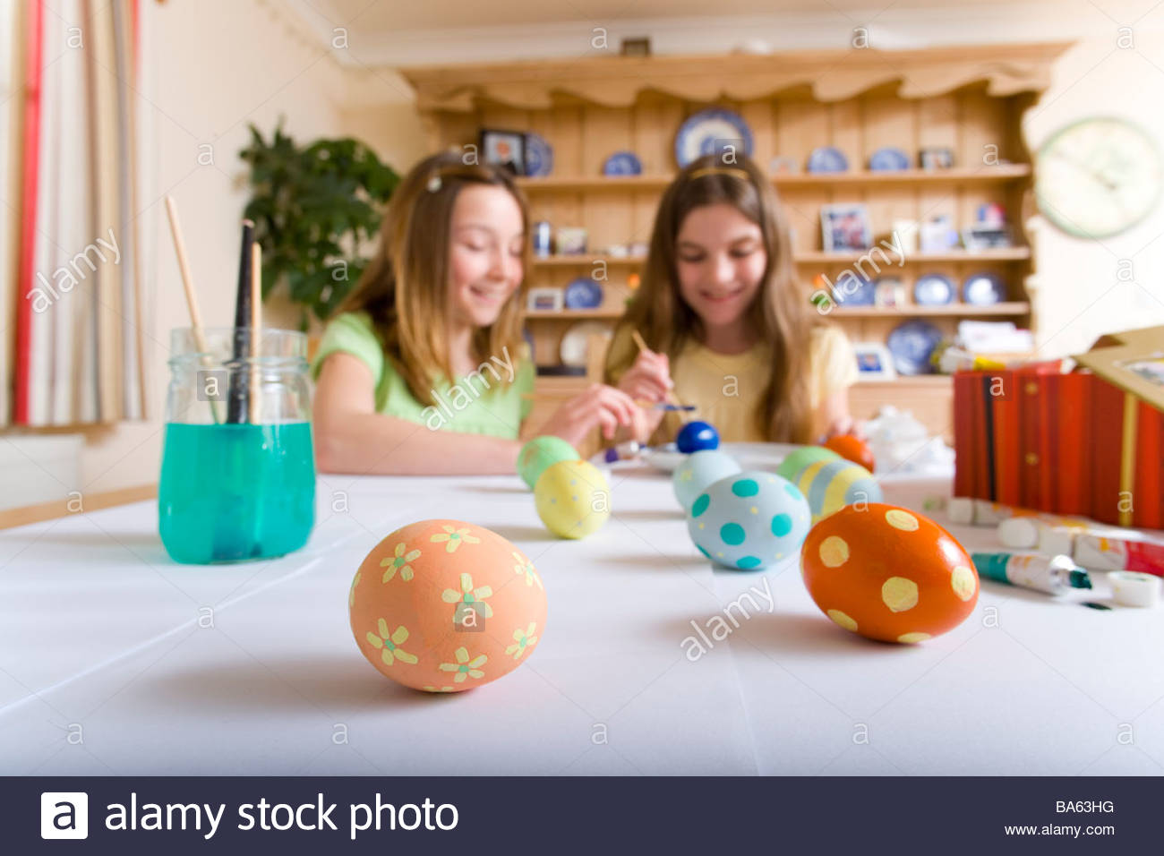 Two young girls decorating Easter eggs - Stock Image