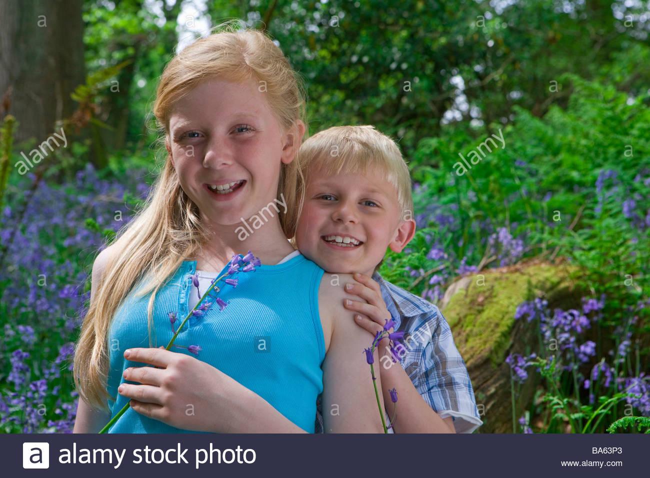 Children sitting on log among bluebell flowers Stock Photo