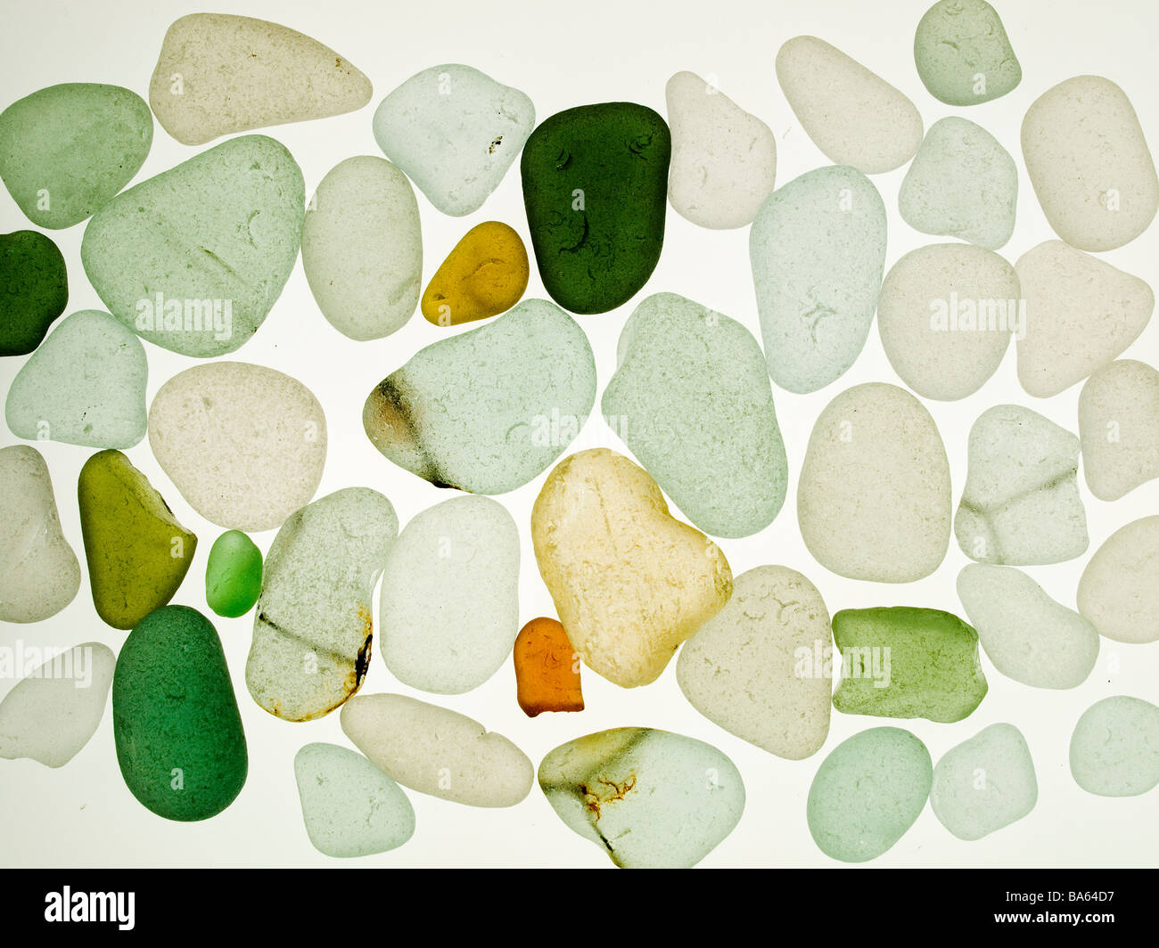 Sea worn glass pebbles collected from a beach displayed on a light box aka 'mermaids tears' and used for - Stock Image
