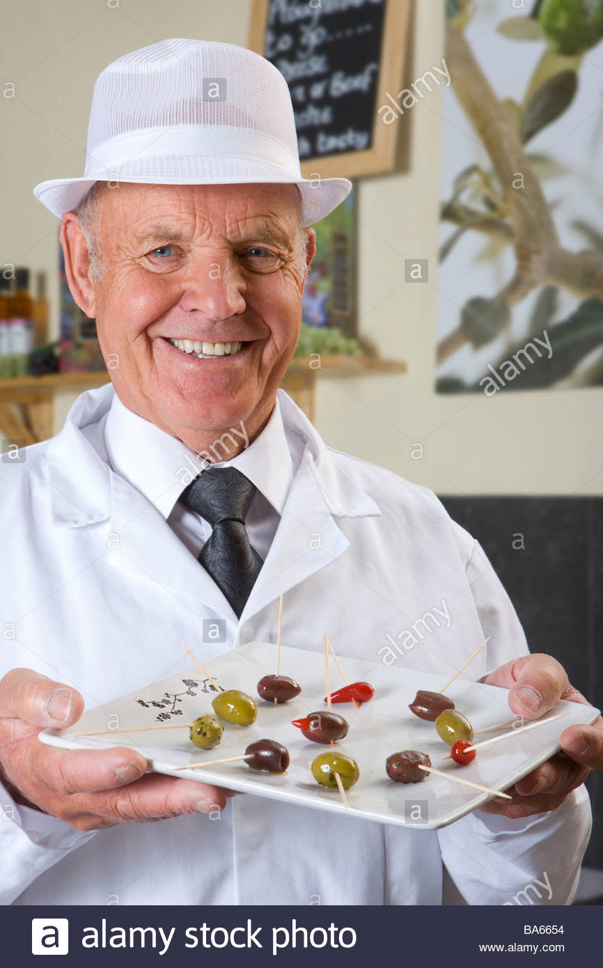 Sales clerk displaying specialty olives - Stock Image