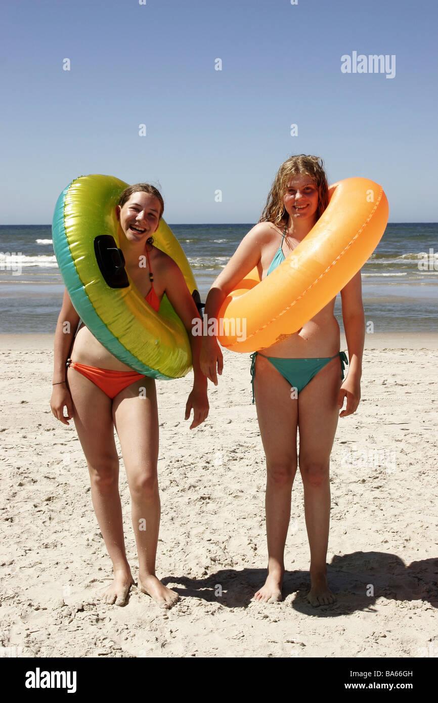 Girls two cheerfully bikini swimming-tires beach stands people teenagers teenagers friends gaze camera fun joy laughter - Stock Image