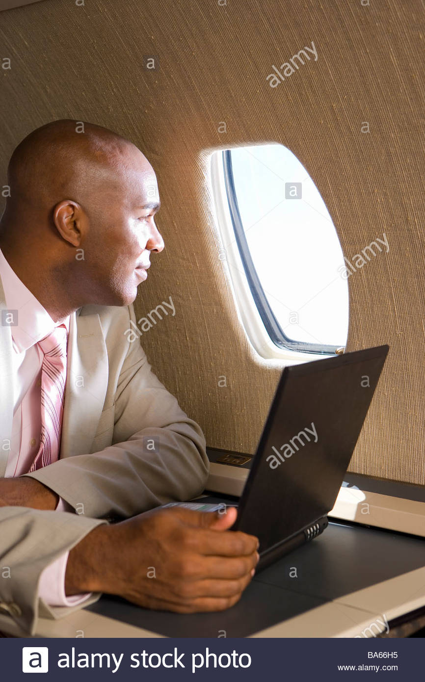 Businessman with laptop computer on aeroplane, looking out window - Stock Image