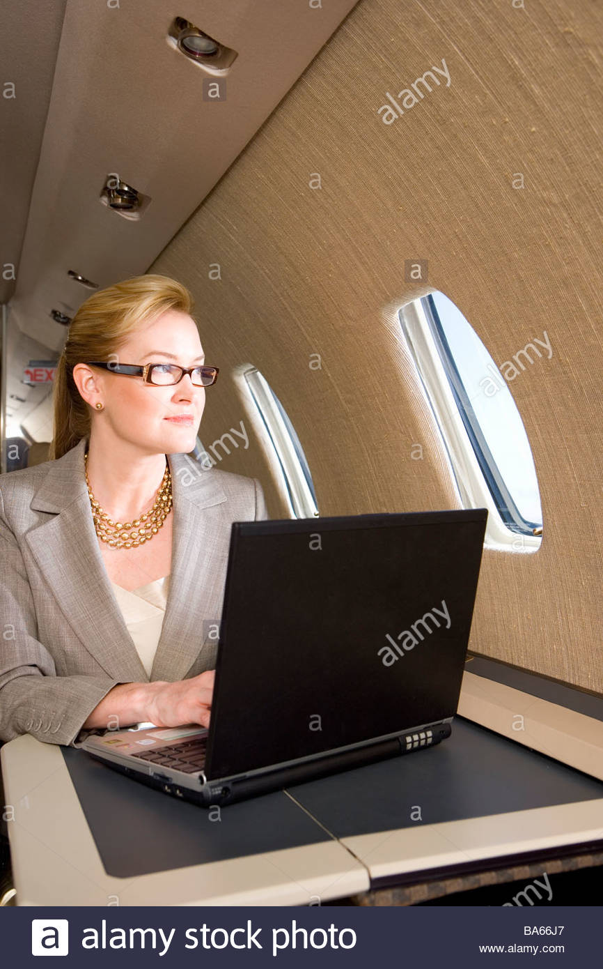 Businesswoman with laptop computer on aeroplane, looking out window - Stock Image