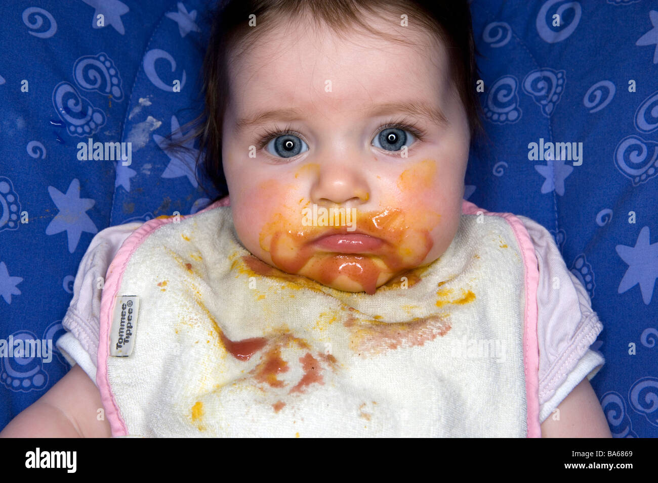 A messy looking baby girl eating food. - Stock Image