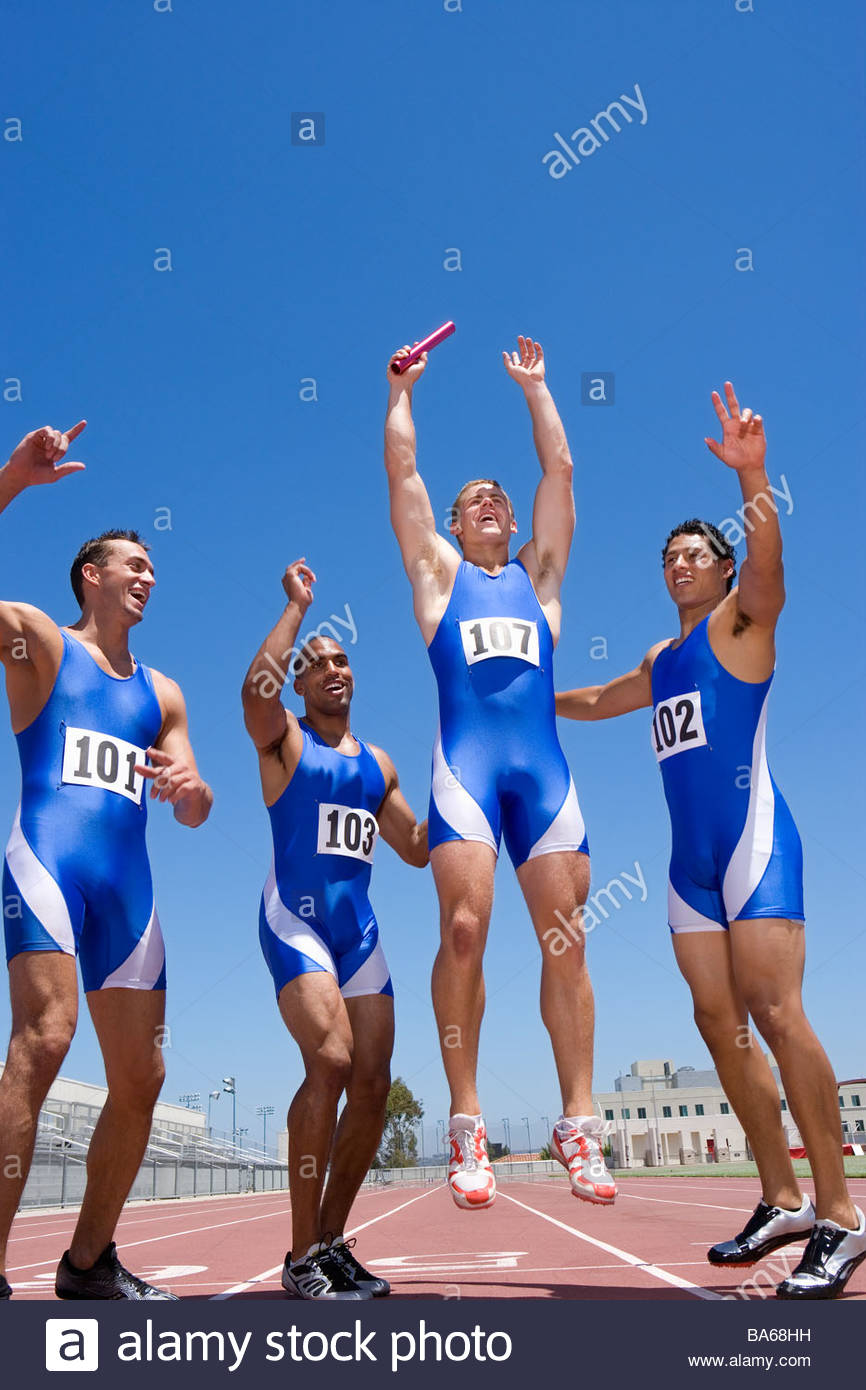 Young male runners cheering after winning race - Stock Image
