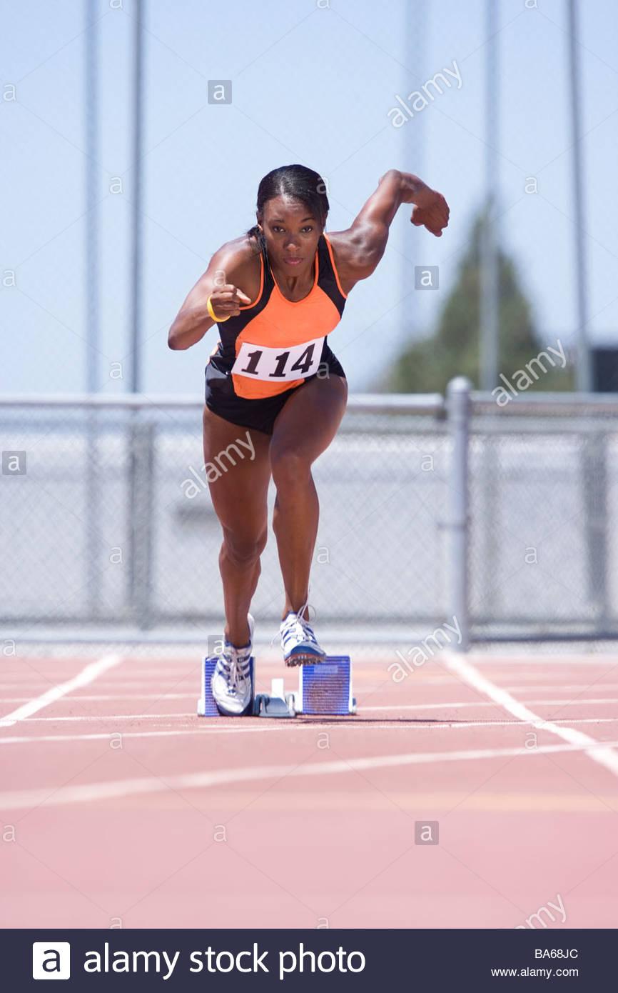 African female runner leaving starting block - Stock Image
