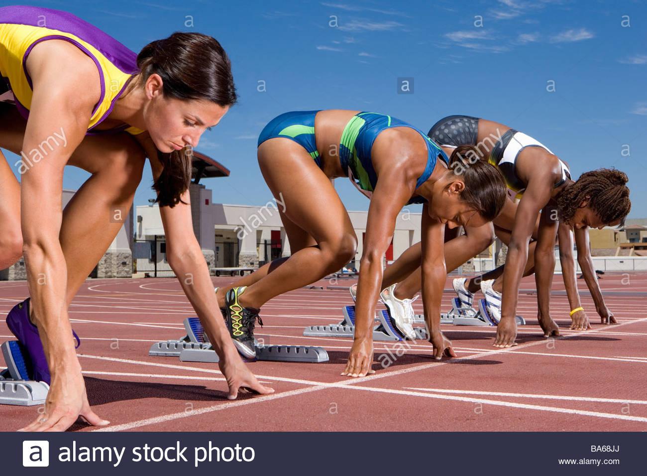 Female runners at starting block kneeling on race track - Stock Image