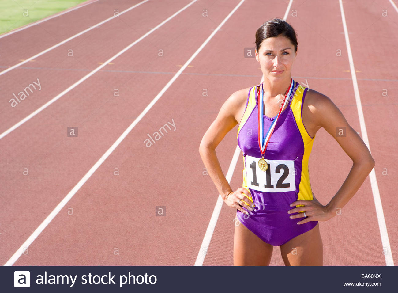 Female athlete with gold medal on race track Stock Photo