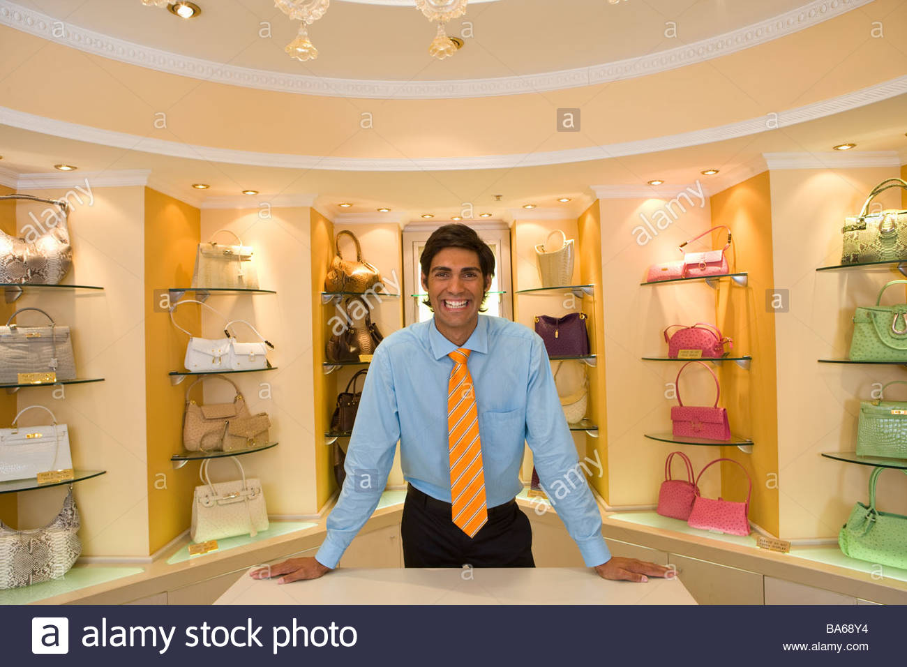 Salesman posing in front of purses - Stock Image