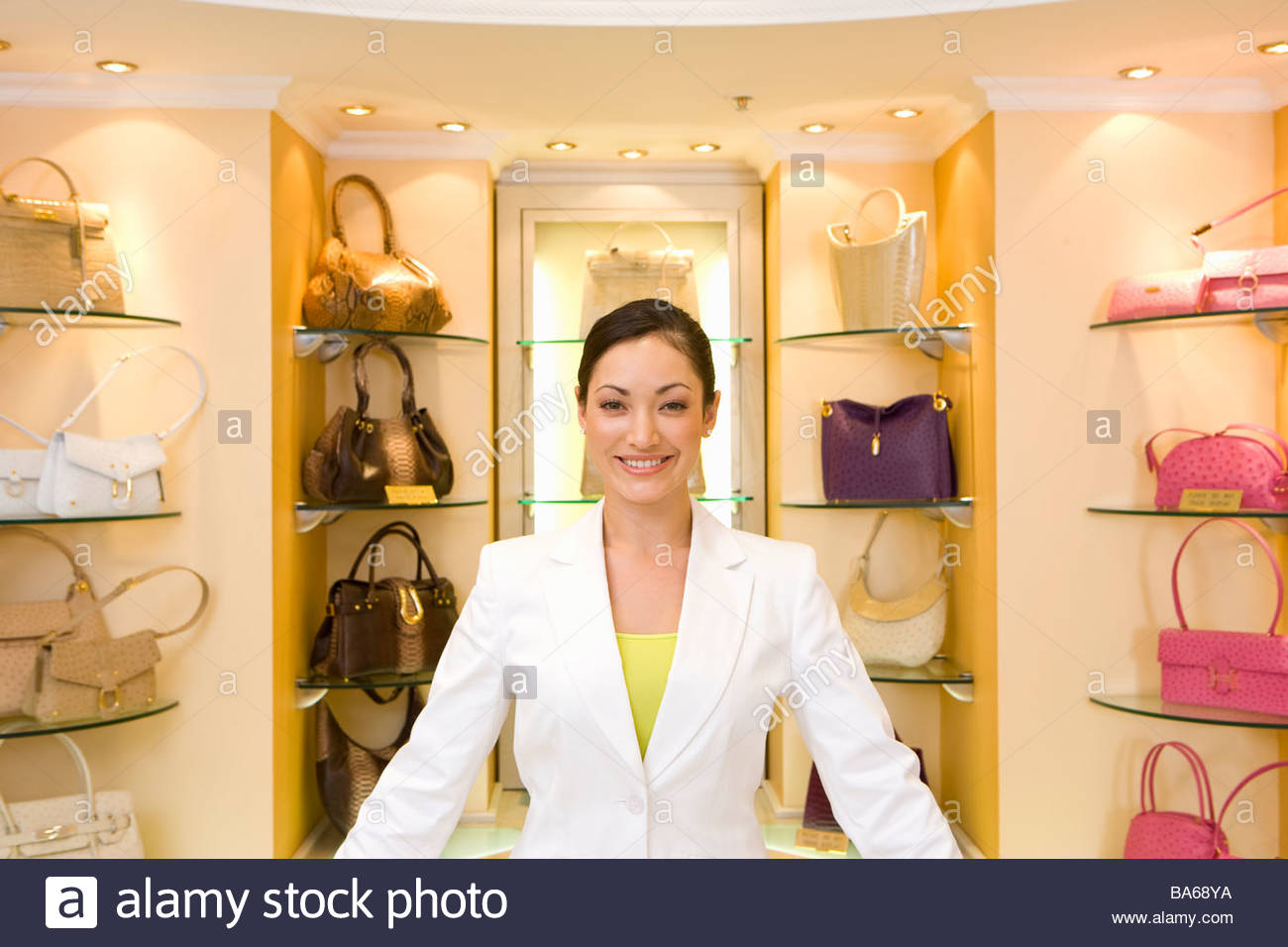Saleswoman posing in front of purses Stock Photo