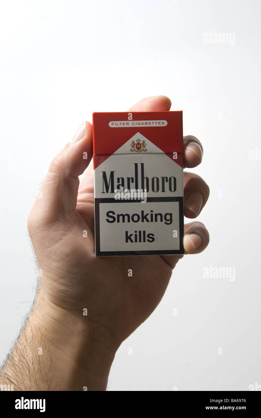 Man's hand holding a red Marlboro cigarettes packet with a smoking kills warning - Stock Image