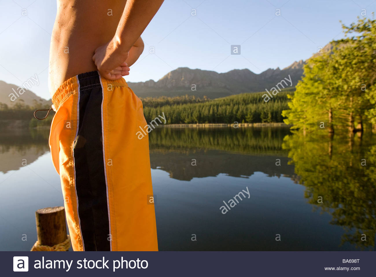 Midsection of man in swim trunks - Stock Image