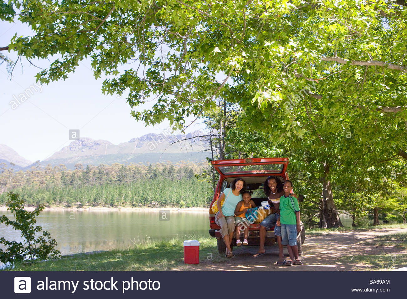 Family picnicking in car by lake - Stock Image