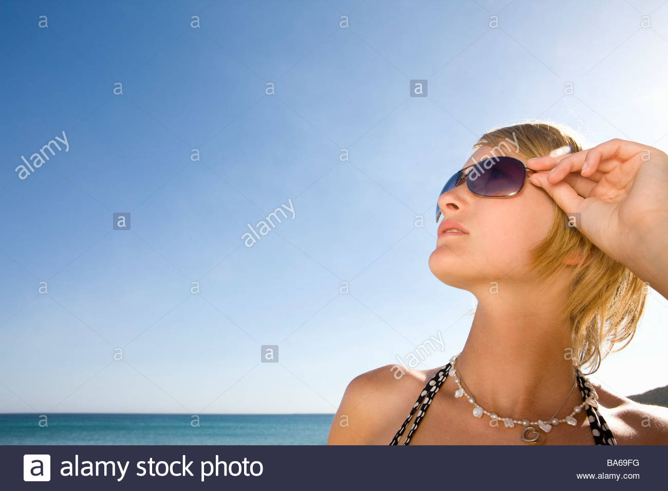 Stylish teenage girl posing on beach - Stock Image