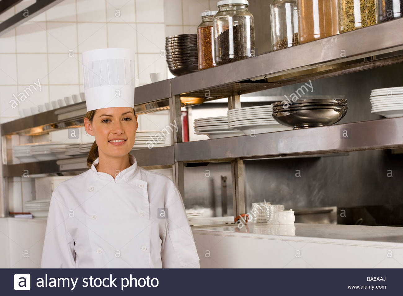 Female chef posing in commercial kitchen - Stock Image