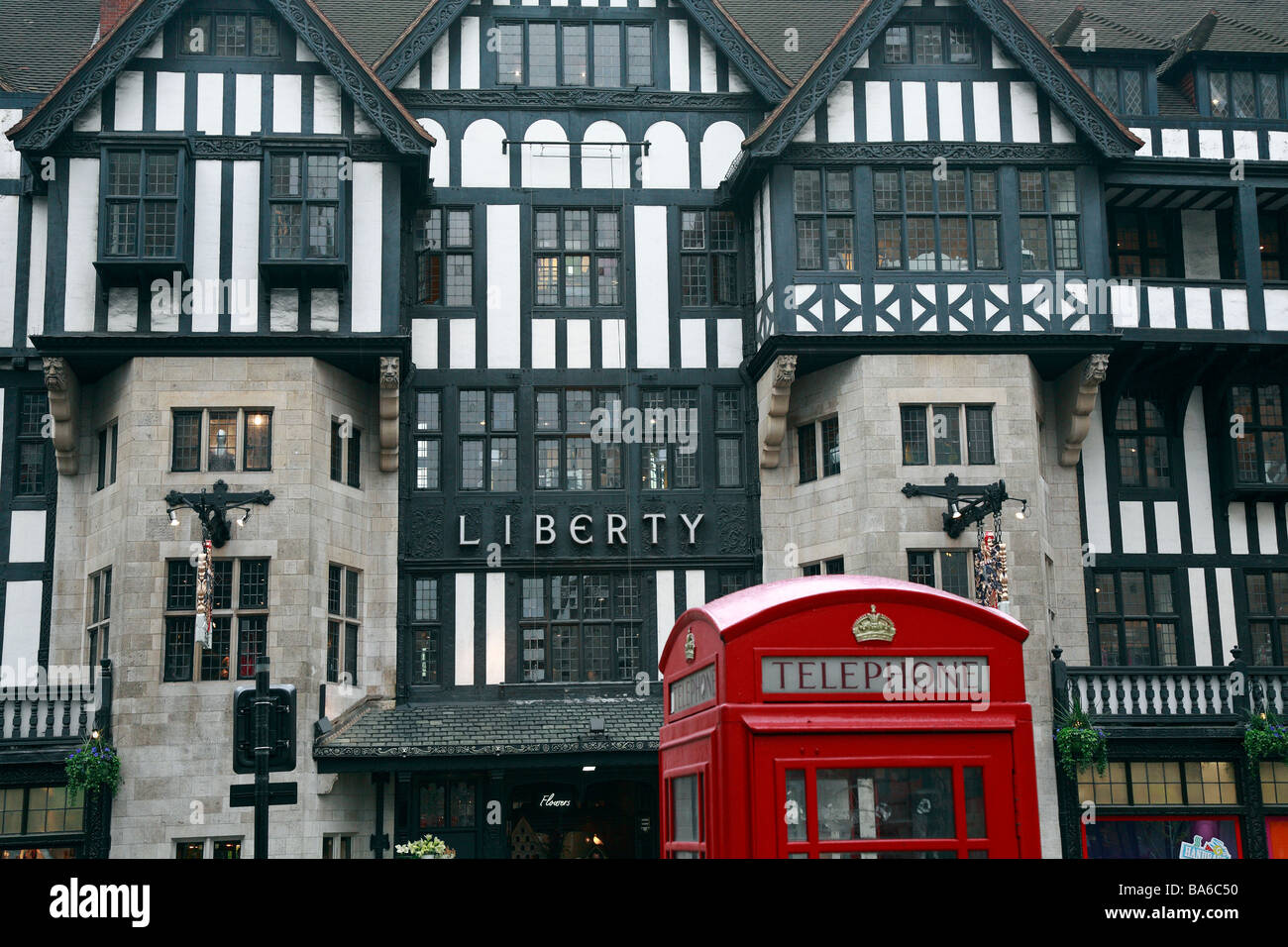 Red Telephone box in front of Liberty department store mock tudor entrance, Great Marlborough Street, London, England, - Stock Image