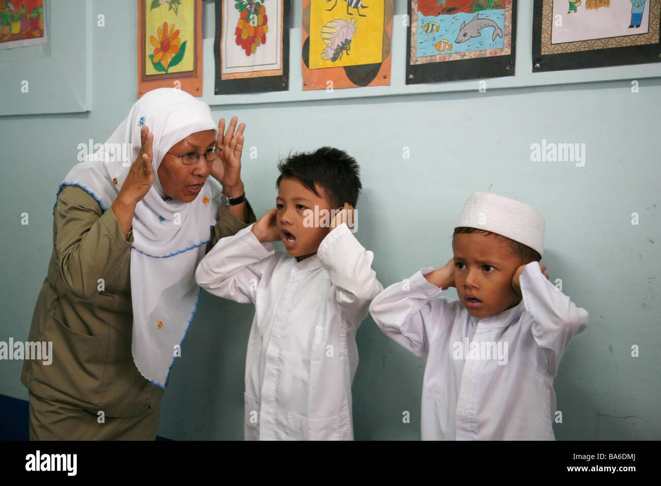 Painet jm0208 indonesia muslim boys taught pray kindergarten banda aceh lost many its children tsunami rebuilt school Stock Photo