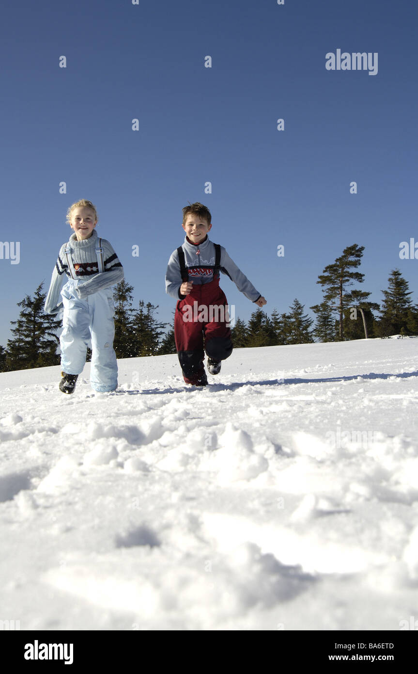 Children boy girls winter-clothing cheerfully runs snow winters winter-landscape vacation vacation leisure time - Stock Image