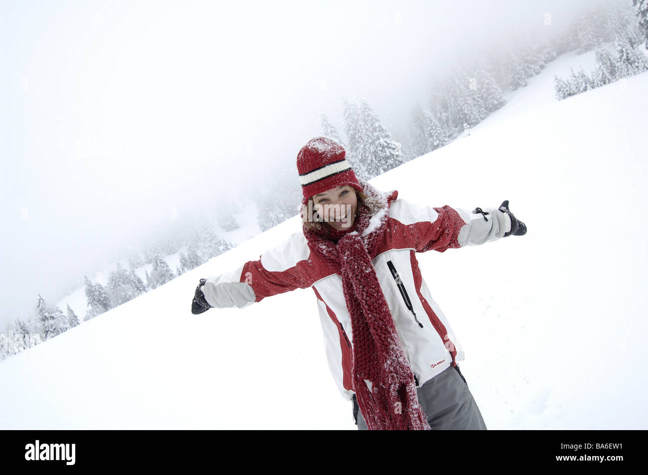 Winter-landscape woman young cap winter-clothing cheerfully laughs gesture joy snow semi-portrait landscape vacation - Stock Image