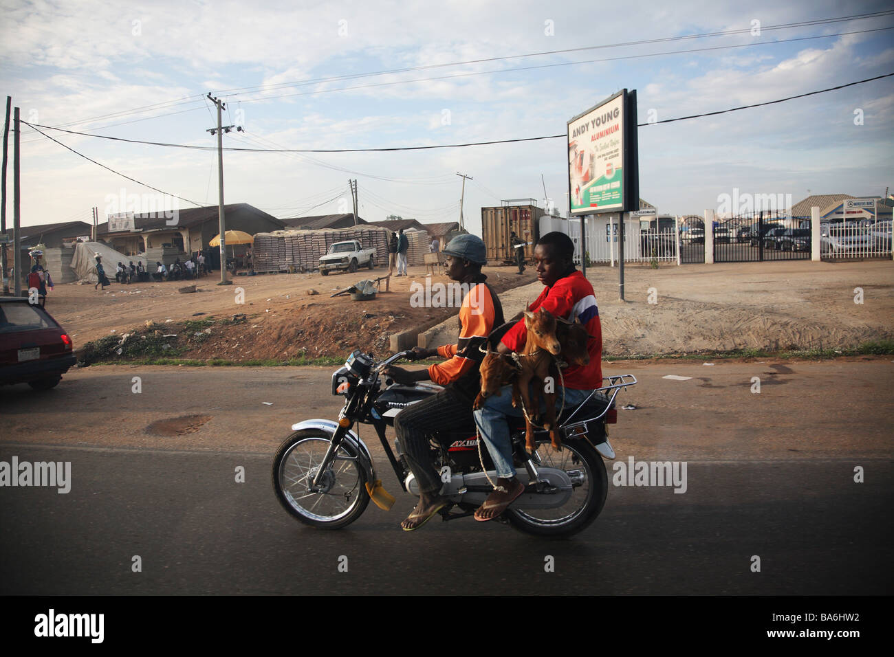Two men and three goats driving along on a motor bike in Abuja, Nigeria. - Stock Image