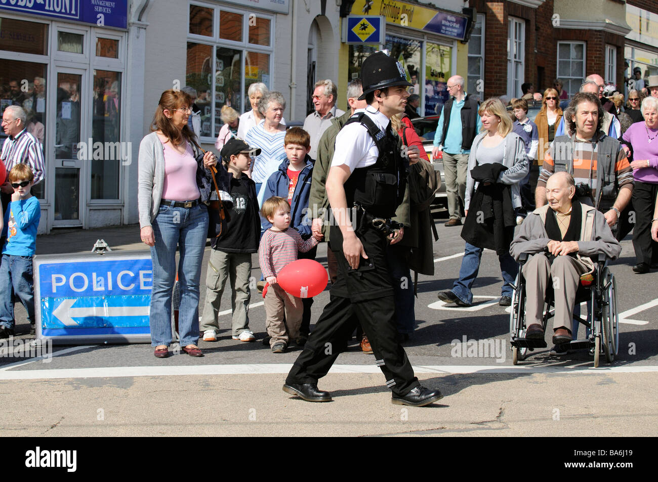 Policeman on crowd and traffic control duty in Petersfield town centre Hampshire England UK Stock Photo
