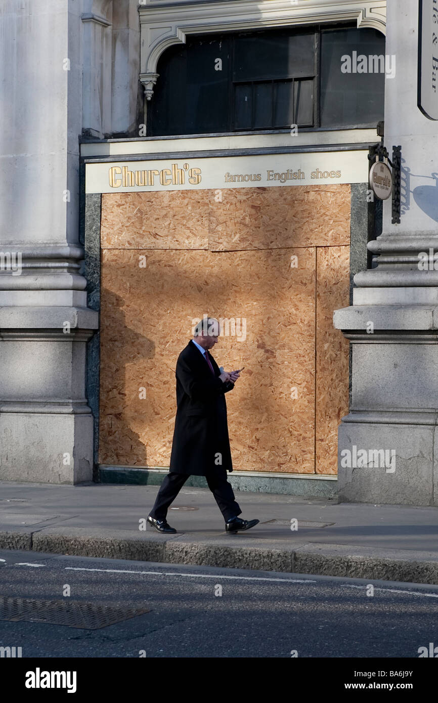 City gent using mobile phone as he walks past boarded up shops prior to G20 protests in City of London, 1 April - Stock Image