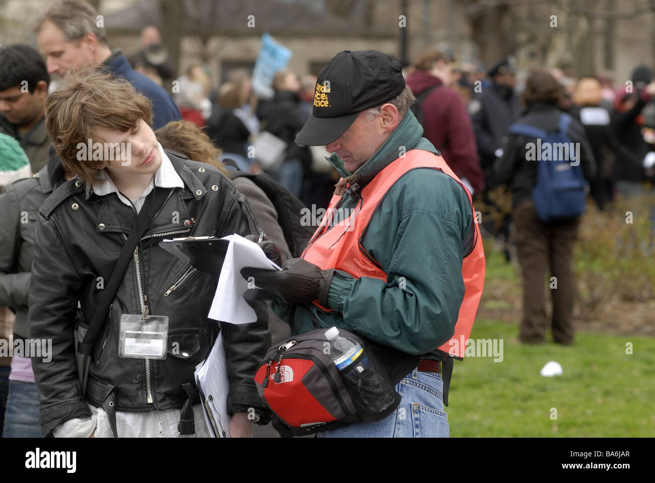 A teenage volunteer left collects signatures on a petition in Battery Park in New York - Stock Image
