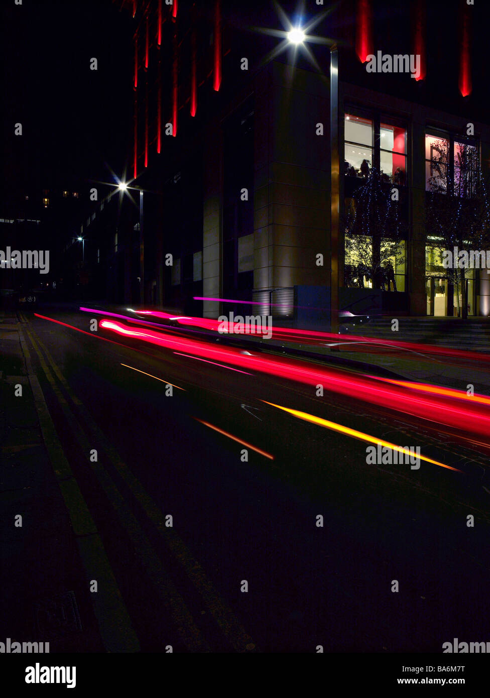 Traffic. Traffic down side street. Busy Road. Hectic. Busy Street. City Life. City Living. Fast Road. Night time. - Stock Image