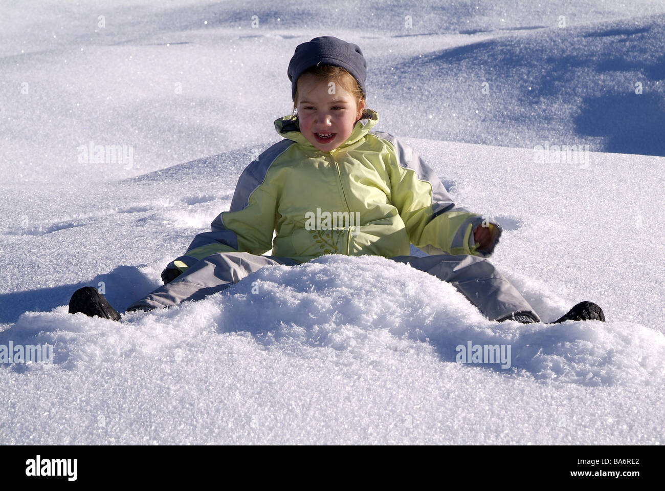 Girls cheerfully winter-clothing snow sit - Stock Image