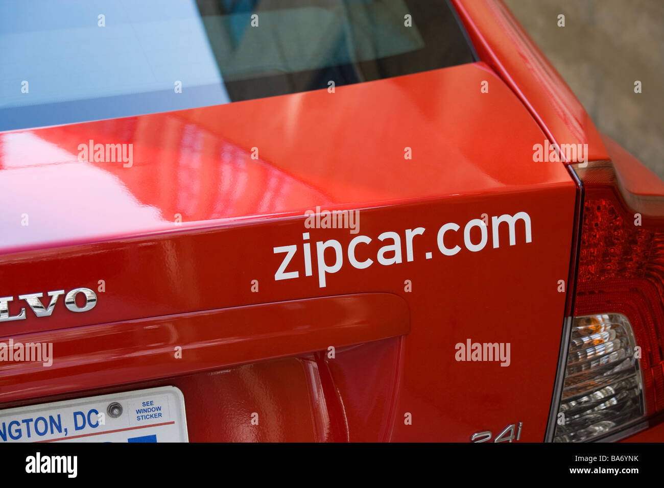 The Zipcar.com internet domain name on the trunk, boot of a red Volvo car in Washington DC, US - Stock Image