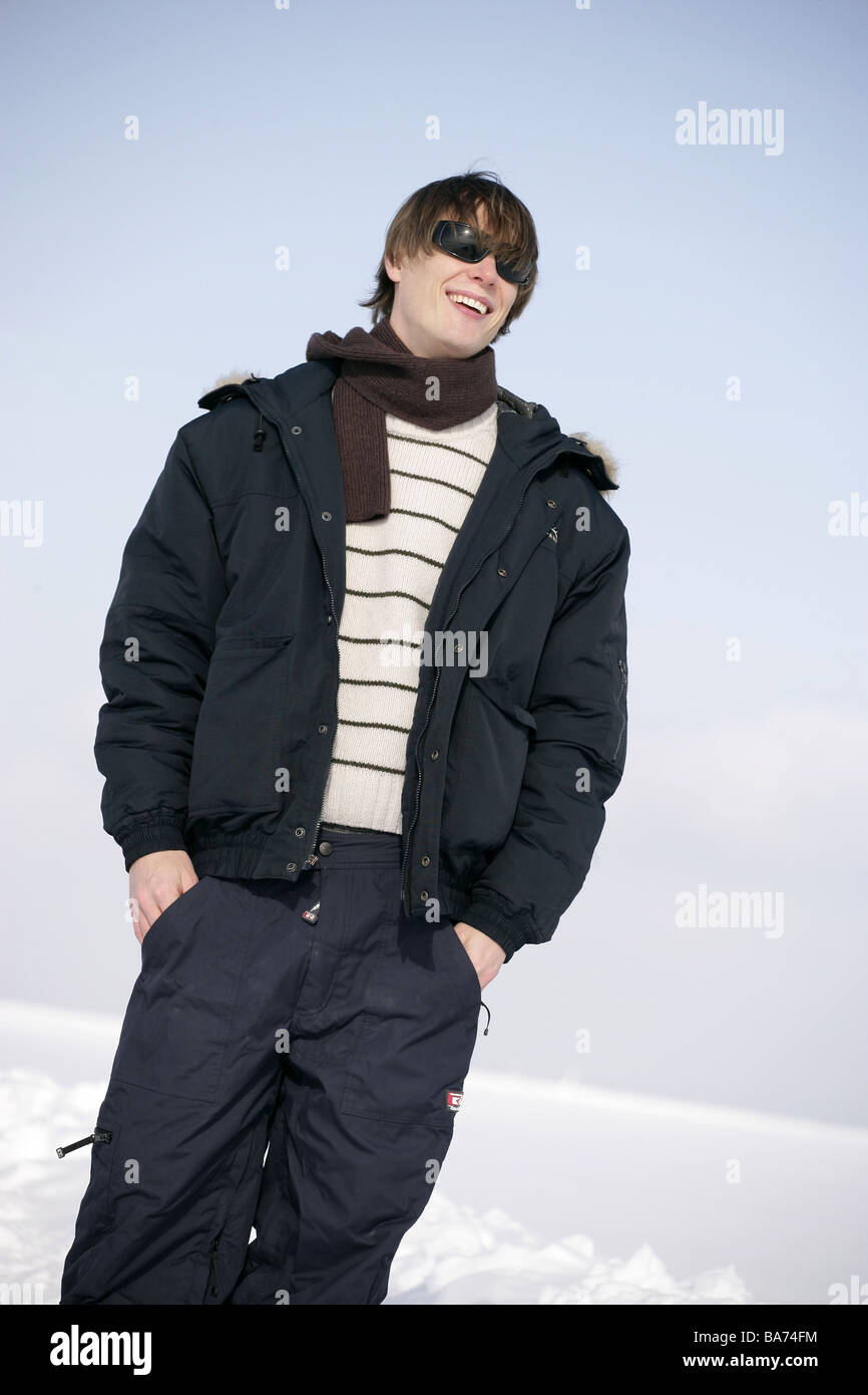 Man young smiles sun glass winter-clothing snow gets along 20-30 years outside look at the side cheerfully jacket - Stock Image