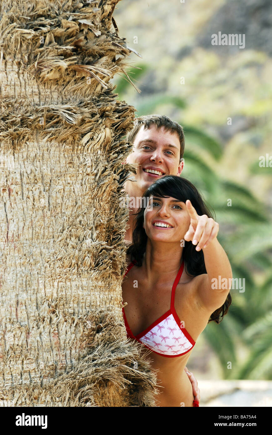 Mate young smiles gesture shows portrait palm trunk detail 20-30 years outside bath-clothing observation relationship - Stock Image